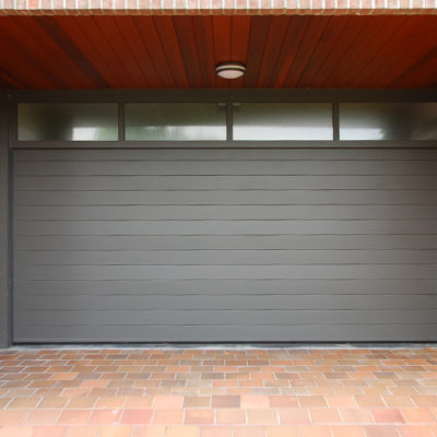 Sectionaalpoort met panelen in gelijnde aluminium profielen, vast bovenraam en bekleding van zijmuren met cederhout
